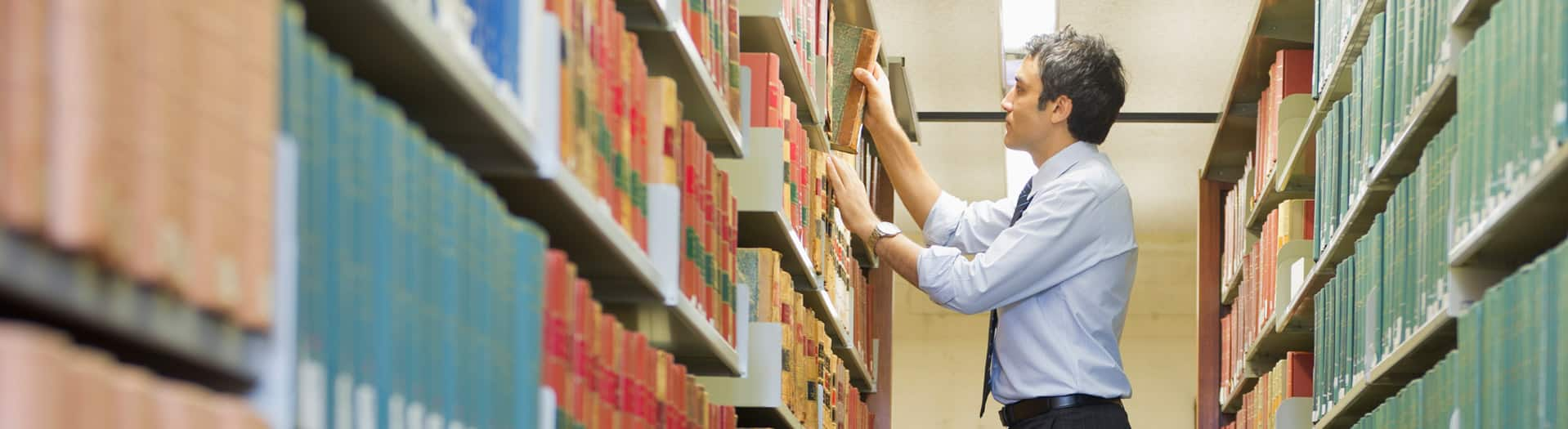 A man putting books back in a library shelf