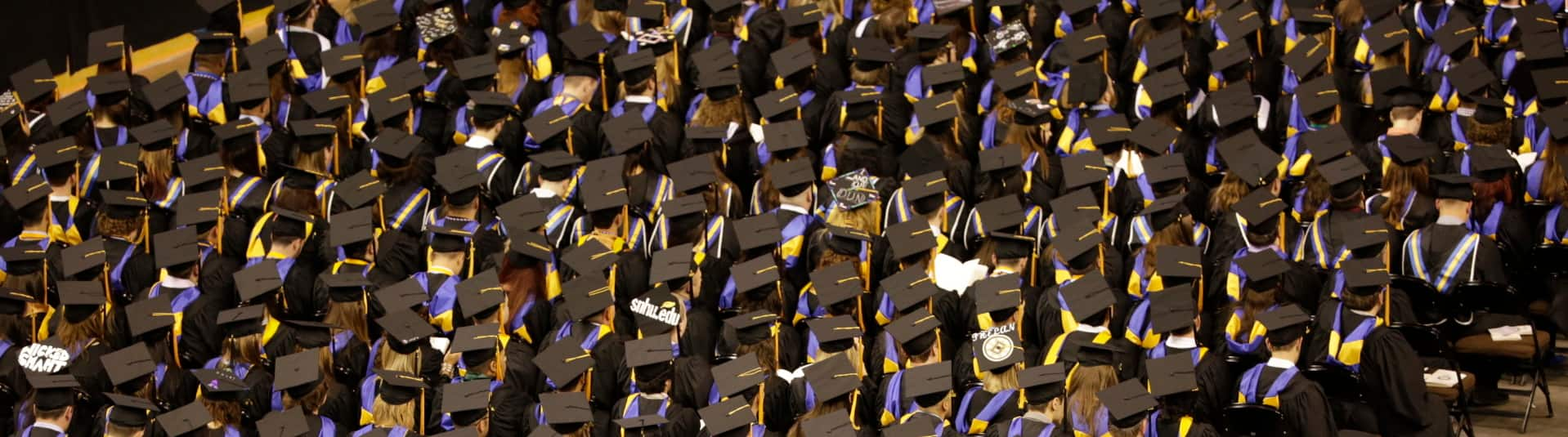 Large group of students wearing caps and gowns at commencement.