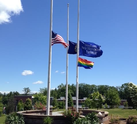 The American, NH, SNHU and Pride flag flying at half-staff on the SNHU campus.