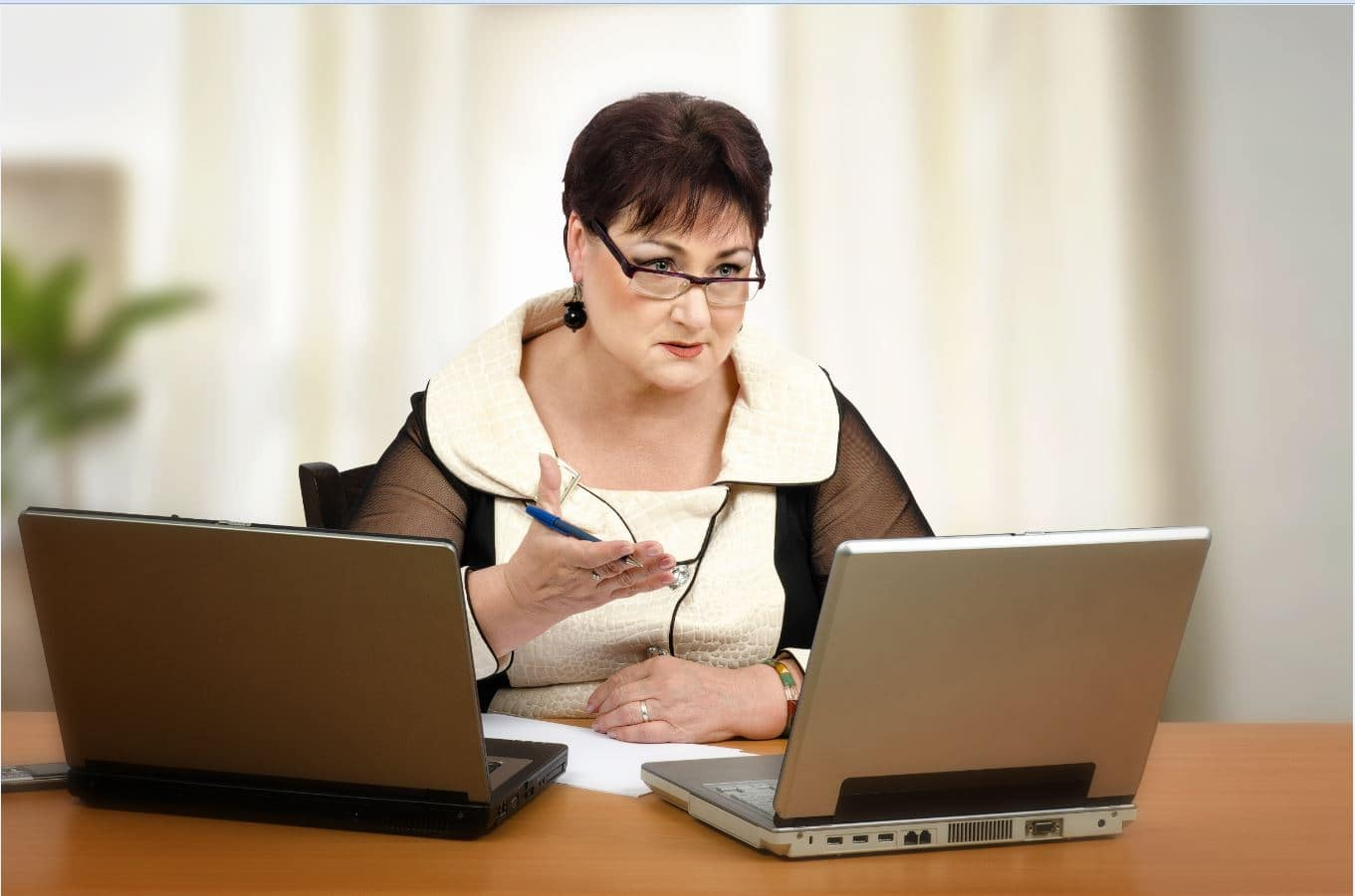 A woman holding a pen with 2 laptops in front of her.