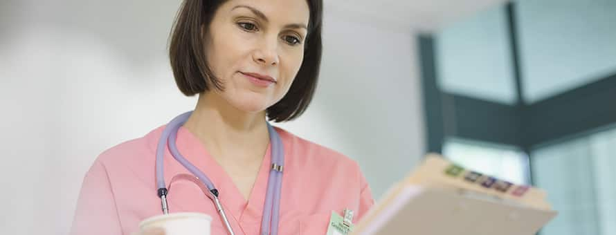 A nurse in light pink scrubs and stethoscope around her neck looking at a medical chart.
