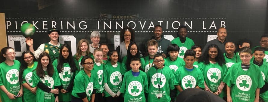 Celtics legend Dana Barros and current rookie Robert Williams join students unveiling a new technology lab at the Madeline English School.