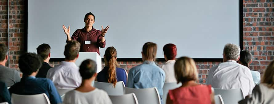 A man with a communications degree at a podium in front of an audience giving an oral presentation.