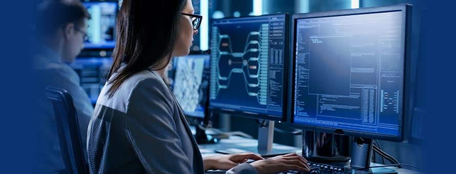 A woman in cyber security working at a computer terminal.