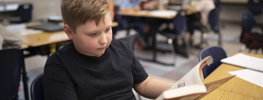 Photo of a boy with dyslexia reading a book.