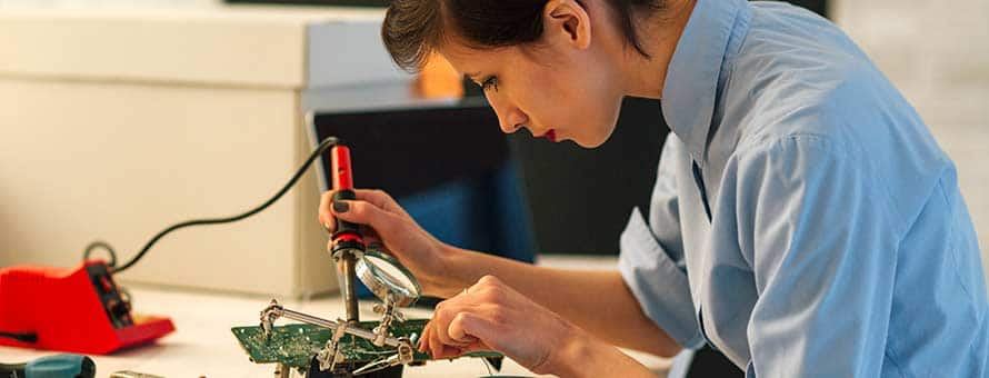 A female electrical engineer using a soldering tool to build an electronic component.