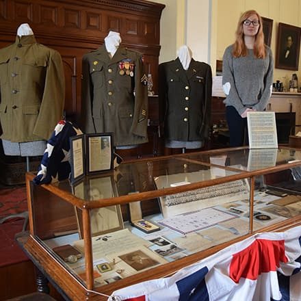 Elizabeth Gitschier standing behind a Civil War display she created including replica uniforms, an easel with maps and letters and a glass display case showing photos and medals.
