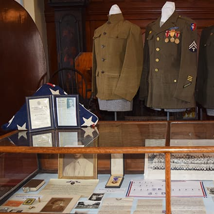 Part of the museum exhibit Elizabeth Gitschier created including Civil War-era replica uniforms and a glass display case containing letters and medals..