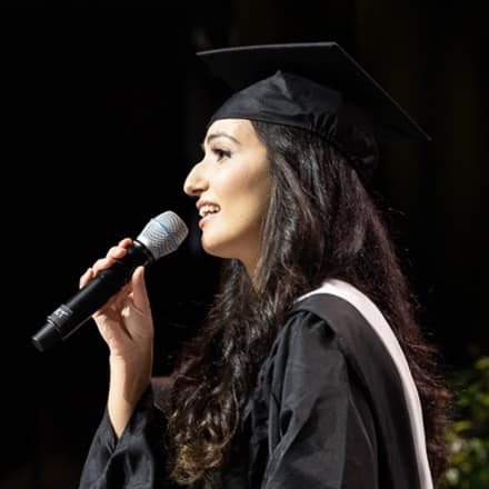 Fatma Salem Pease in her cap and gown holding a microphone and singing the national anthem at SNHU's 2019 Commencement.
