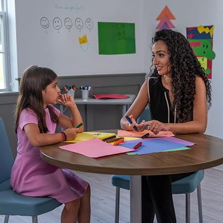 Fatma Salem Pease working with a young girl at a table covered with construction paper and markers.