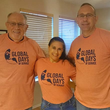 Three members of the SNHU community wearing orange Global Days of Service T-shirts after participating in a project.