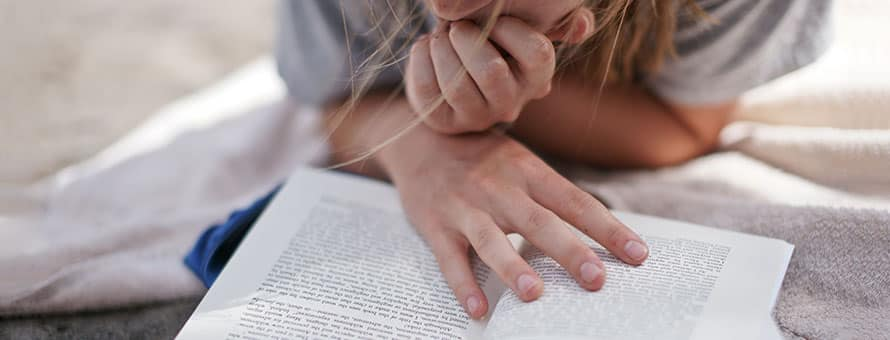 Female student reading a book on a blanket