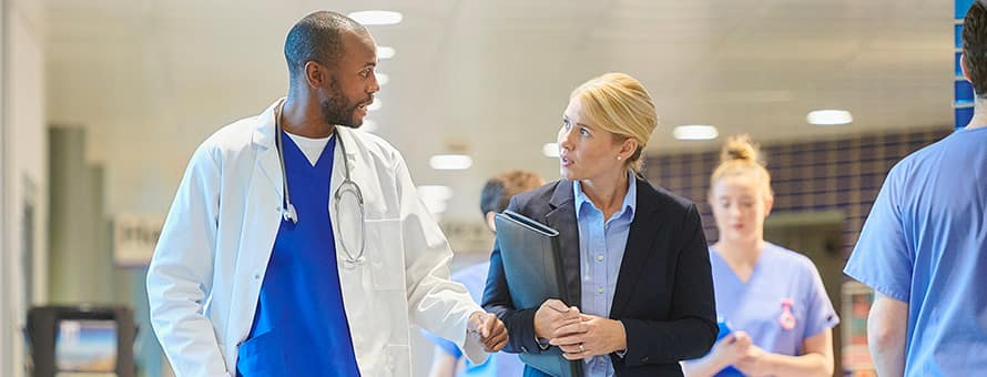 A healthcare administrator speaking with a doctor as they walk down a hospital hallway.