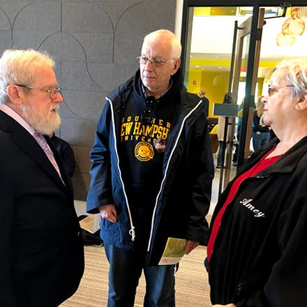 Three members of the Class of '69 talking during SNHU's Homecoming Weekend.