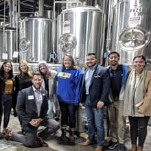 Eight members of the SNHU alumni community during a brewery tour.