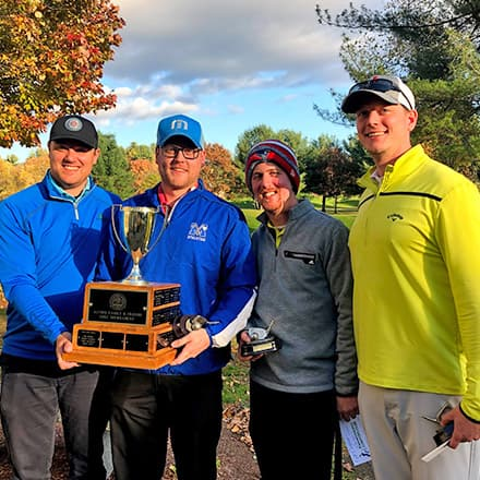 Four men holding a trophy following a golf tournament during SNHU's Homecoming Weekend.