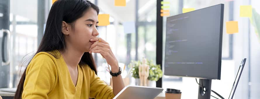 A woman looks at a computer screen studying how to become a software engineer