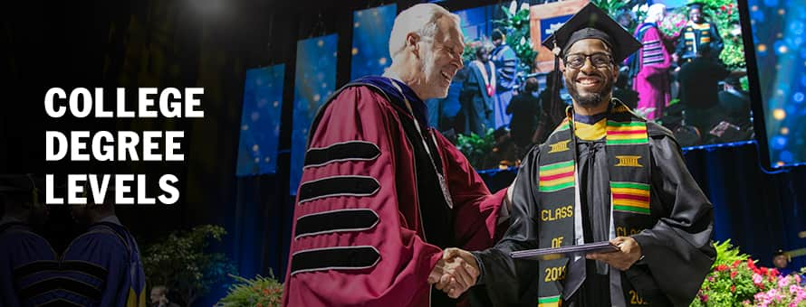 A man in graduation cap and gown shaking hands with a university president as he receives his degree and the text College Degree Levels.