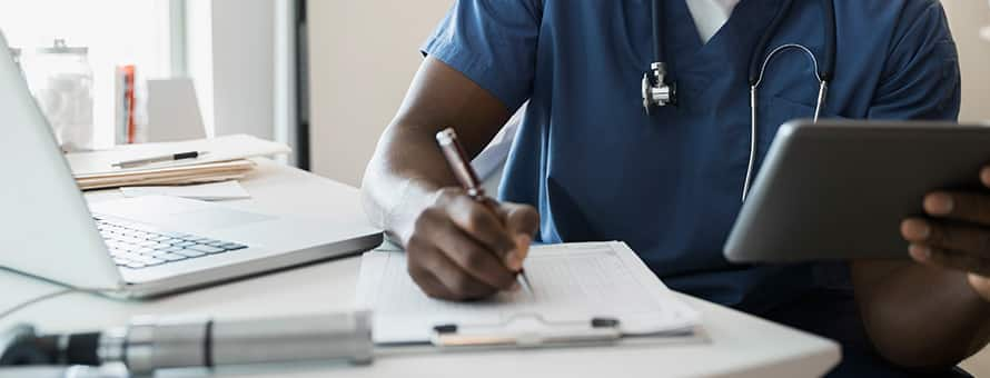 A male nurse wearing blue scrubs and a stethoscope writing in a medical chart.