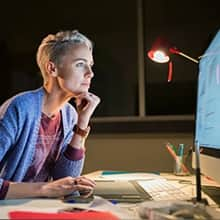 A woman looking at a computer monitor and using marketing analytics to optimize a digital campaign.