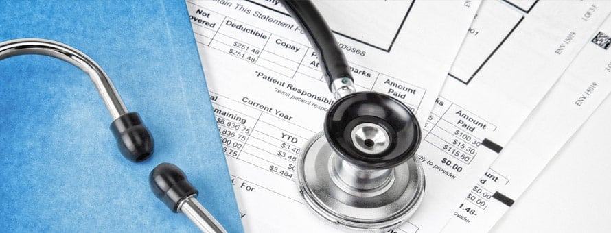 A stethoscope on top of a pile of medical bills.