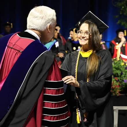 Jessica Bryant wearing cap and gown and receiving her degree from SNHU President Paul LeBlanc.