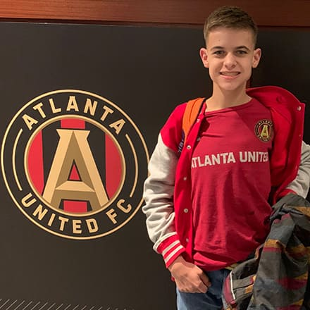 Reese Silverman wearing an Atlanta United T-shirt and standing beside the Atlanta United FC logo.