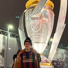 Reese Silverman wearing an Atlanta United jersey and hat standing in front of a large class sculpture of the MLS Cup.