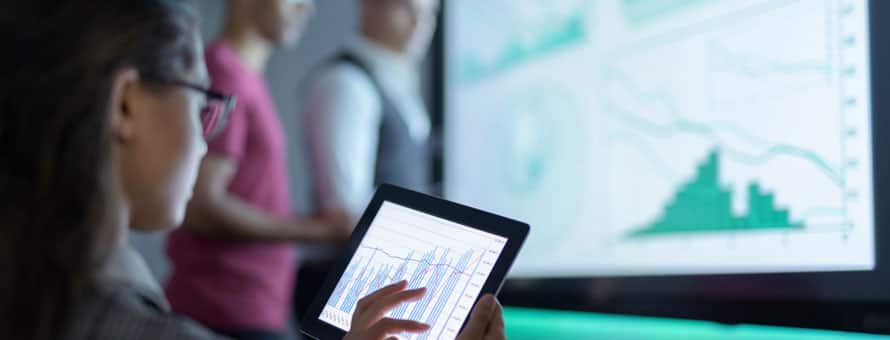Woman holding a tablet while data graphs are being projected in the background