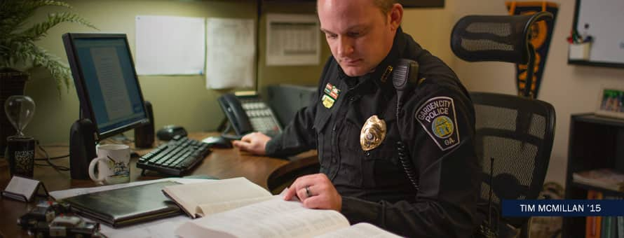 Tim McMillan in his police uniform working at his desk with text Tim McMillan '15