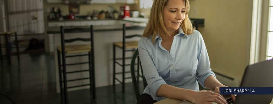 "Woman sitting in her kitchen typing on a laptop, with text ""Lori Sharp '14"""