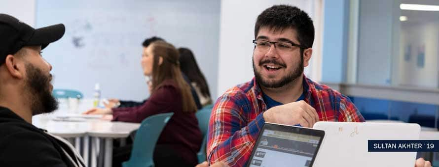 Computer science student with glasses smiles at classmate in classroom.