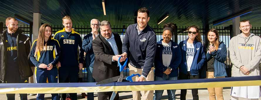 SNHU officials cut a ribbon with big scissors to officially open Penmen Stadium