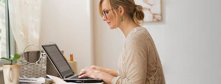 A blonde woman wearing glasses working on her laptop.