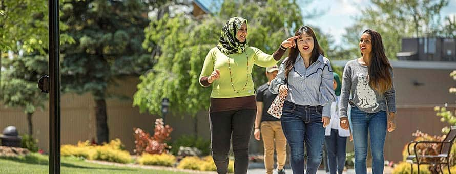 Three women walking down a path on a college campus.