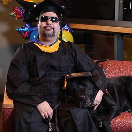 Ricardo Scarello wearing his cap and gown with his service dog, Puck, laying beside him.