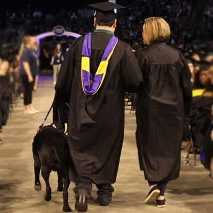 Ricardo Scarello walking down an aisle at SNHU commencement ceremony with his service dog, Puck, and a woman assisting him.
