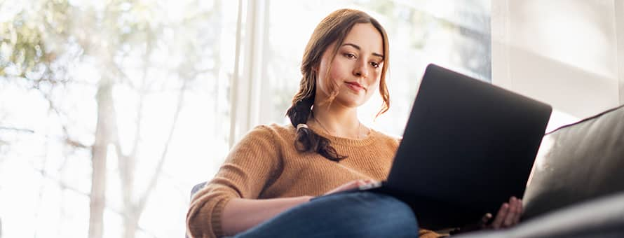 A woman sitting on her couch working on her MA degree on her laptop