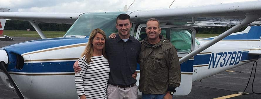 SNHU student Ben Cumming standing in front of Cessna airplane with his mother and father.