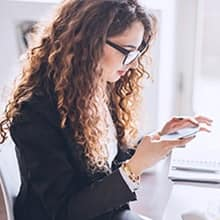 A woman using her cell phone to track the results of a social media marketing campaign.