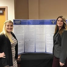 Two undergraduate students in front of a large poster displaying their research.