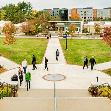 A college quad with people walking along a series of sidewalks in a geometric pattern.