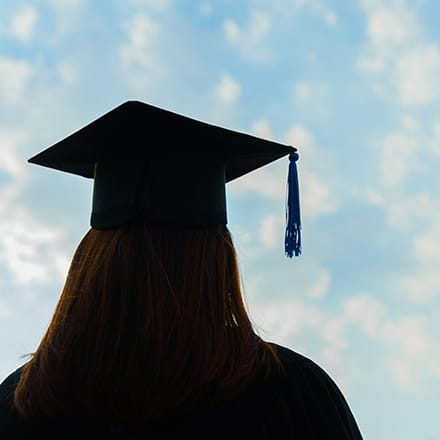 A college graduate on Military Spouse Appreciation Day, wearing her mortarboard and looking toward the sky.