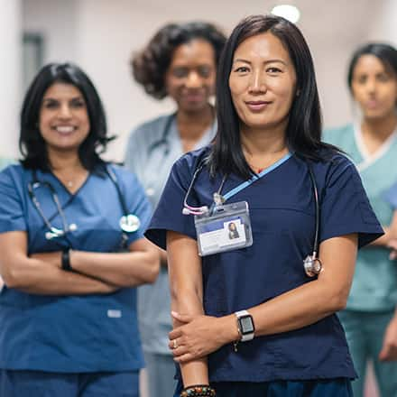 4 nurse leaders wearing medical scrubs and stethoscopes.