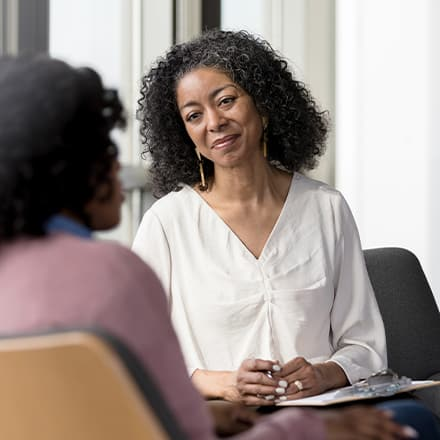 A female mental health counselor speaking with a client.