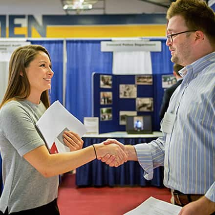 A woman trying to find the right career shaking hands with a man at a career fair.