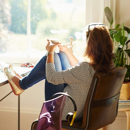 A woman relaxing at her home office with a cup of coffee and feet up on her desk.