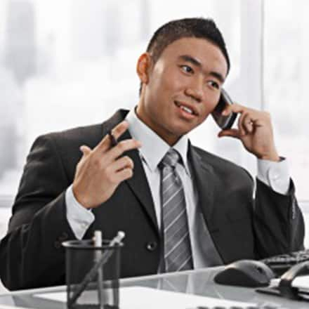 A communications professional talking on the phone at his desk.