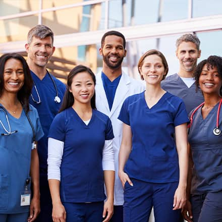 A diverse group of seven nurses wearing scrubs, practicing cultural competencies in nursing.