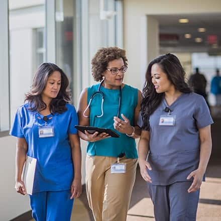 Three female nurses at different career levels walking in a hospital corridor.